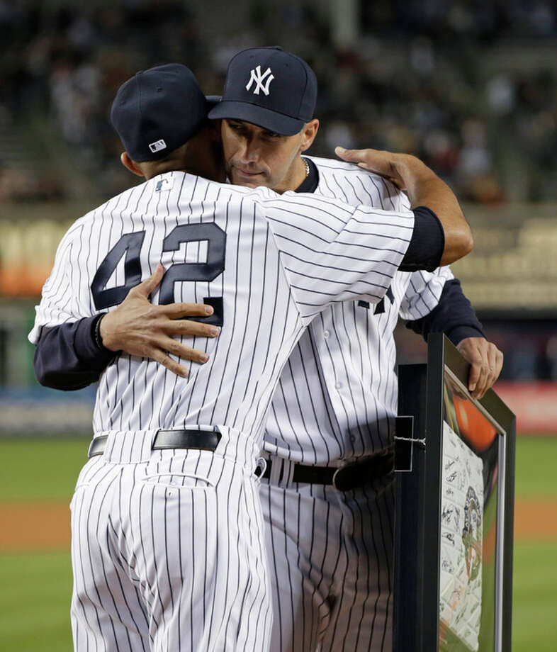 New York Yankees starting pitcher Andy Pettitte, who pitched his final game at Yankee Stadium on Sunday, embraces relief pitcher Mariano Rivera, who is retiring at the end of the season, after Rivera and Derek Jeter presented Pettitte with a base from Sunjday's game, Wednesday, Sept. 25, 2013, in New York. (AP Photo/Kathy Willens) / AP