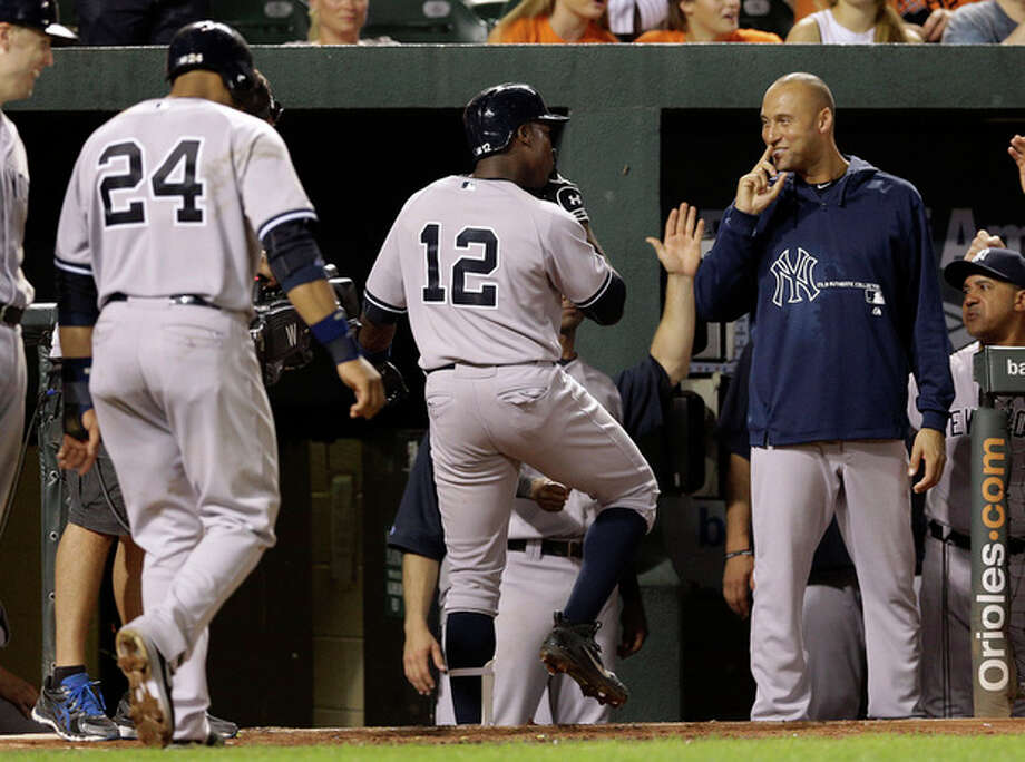 New York Yankees' Alfonso Soriano (12) and Derek Jeter, right, gestures after Soriano drove in teammate Robinson Cano (24) on a home run in the eighth inning of a baseball game against the Baltimore Orioles, Tuesday, Sept. 10, 2013, in Baltimore. New York won 7-5. (AP Photo/Patrick Semansky) / AP