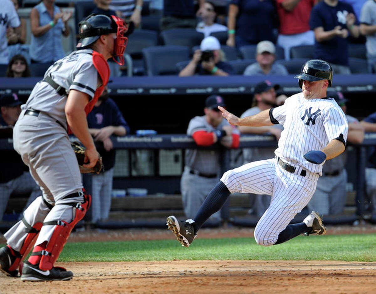 New York Yankees' Brett Gardner scores on a double by Mark Reynolds (not shown) as Boston Red Sox catcher Ryan Lavarnway, left, waits for the ball during the eighth inning of a baseball game Saturday, Sept. 7, 2013, at Yankee Stadium in New York. (AP Photo/Bill Kostroun)