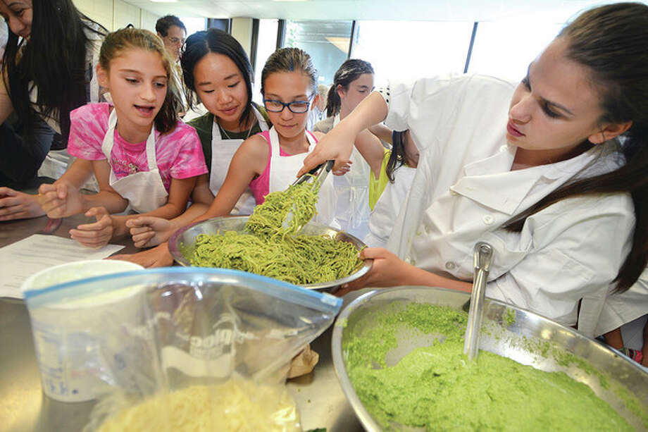 Hour photo / Alex von KleydorffTenth-grader Lilli Garcia works with her group on a Great Green Pasta dish made with spinach, avocado, onion and cheese to compete in Iron Chef at Norwalk High School.