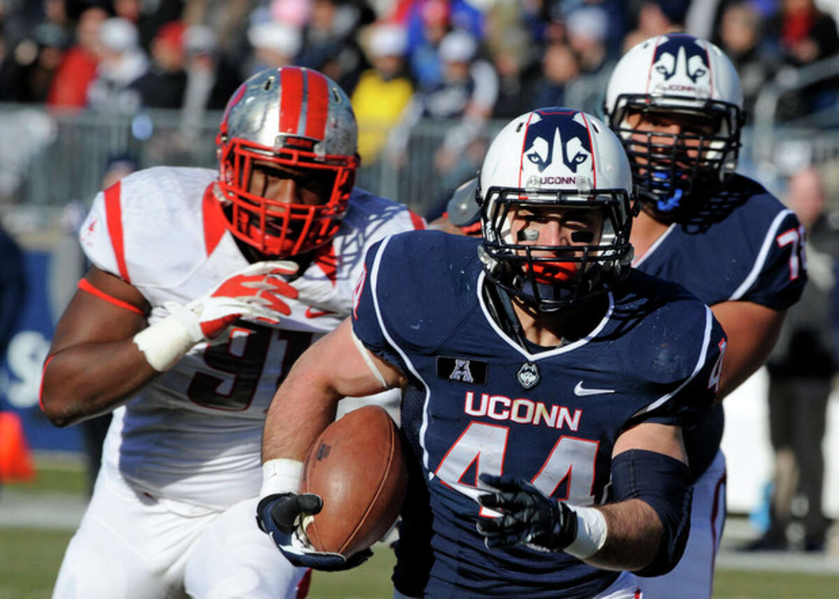 Connecticut running back Max DeLorenzo (44) runs for a touchdown while being pursued by Rutgers defensive lineman Darius Hamilton (91 left, during the first half an NCAA college football game in East Hartford, Conn., on Saturday, Nov. 30, 2013. (AP Photo/Fred Beckham)