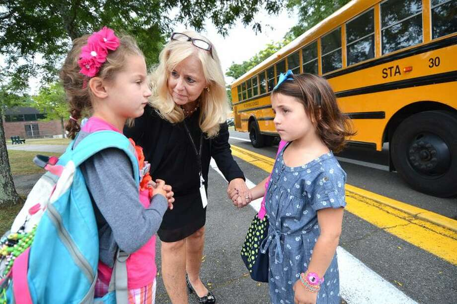 Hour Photo/Alex von Kleydorff. Miller Driscoll Principal Cheryl Jensen-Gerner helps kids find their way after arriving by school bus to their first day of school in Wilton