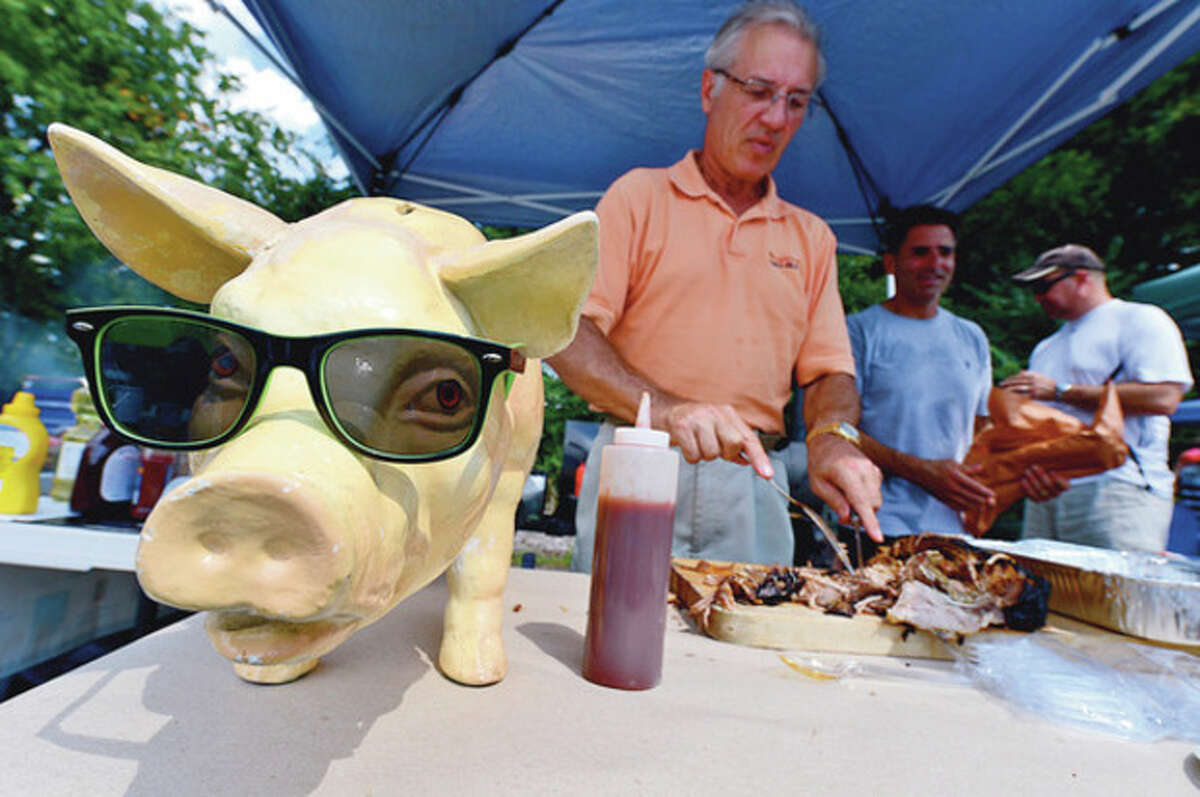 Hour photos / Erik Trautmann Jeff Sciallo and the Lazy Bones team gear up for the barbeque competition at the Blues, Views and BBQ Festival in Westport Saturday. The festival's cool-shaded mascot pig decorates their table.
