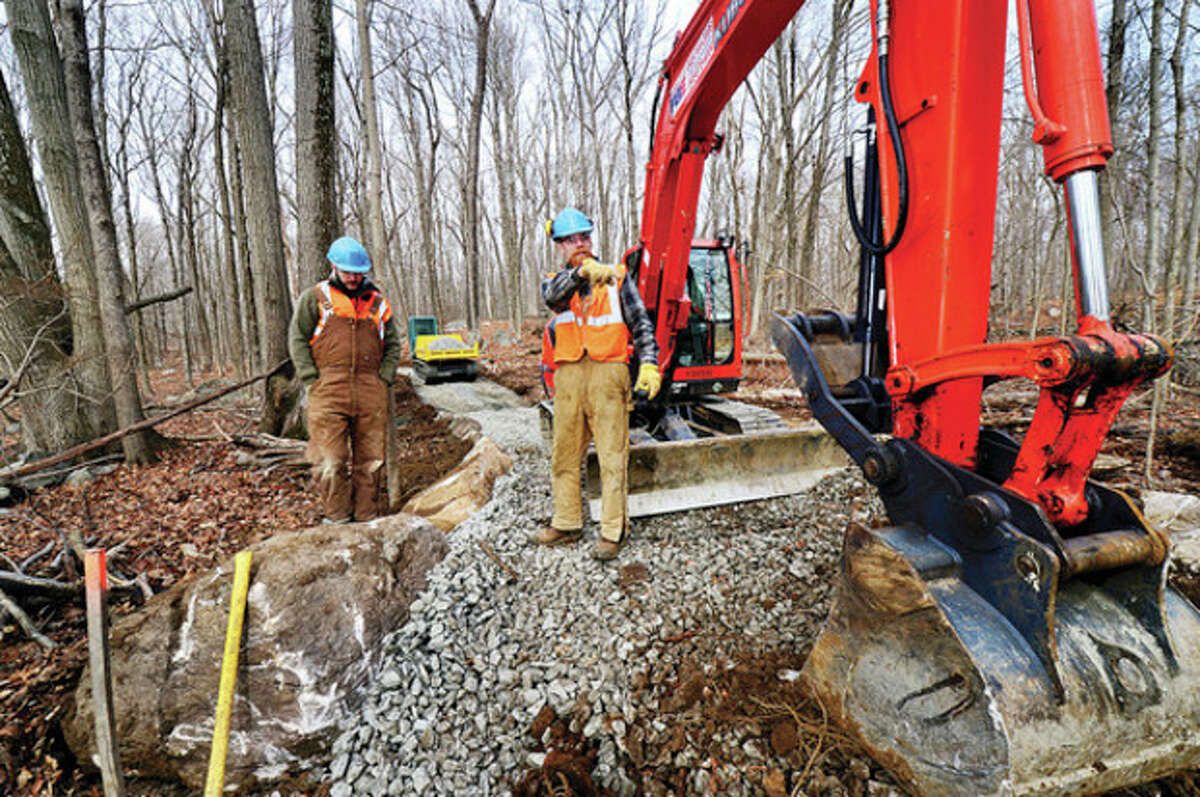 Hour photo / Erik Trautmann Alex Hoffmeier and Josh Ryan, employees from Vermont-based Timber & Stone, LLC, construct the demonstration leg of the Norwalk River Valley Trail in Wilton. The half-mile demo trail is 70 percent complete, and is expected to be finished in three weeks.