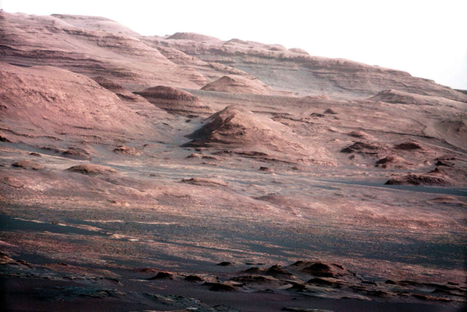 FILE - This file image provided by NASA shows the base of Mount Sharp on Mars. The Curiosity rover is set to drive toward the mountain in mid-February after drilling into a rock. The image was taken by Curiosity's 100-millimeter Mast Camera on Aug. 23, 2012. Scientists enhanced the color in one version to show the Martian scene under the lighting conditions we have on Earth, which helps in analyzing the terrain. (AP Photo/NASA/JPL-Caltech/MSSS, File) / NASA/JPL-Caltech/MSSS