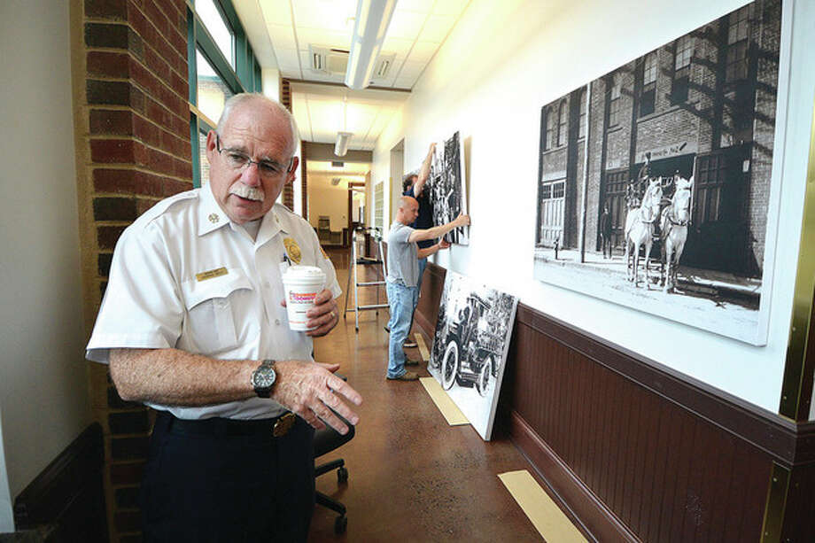 Hour Photo/Alex von KleydorffNorwalk Assistant Fire Chief Laurence Reilly talks about the installation of vintage Fire Dept. photographs in a walkway gallery at the New Norwalk Fire Department Headquaters on Connecticut Avenue.