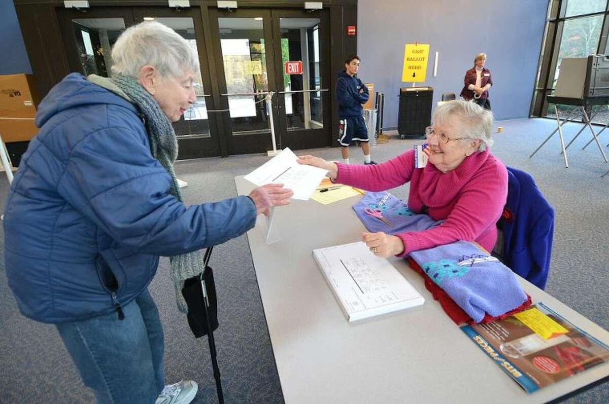 Head Ballot Clerk Ann Klotz hands Lois Kuperschmid a ballot during voting at Wilton High School on Election Day.