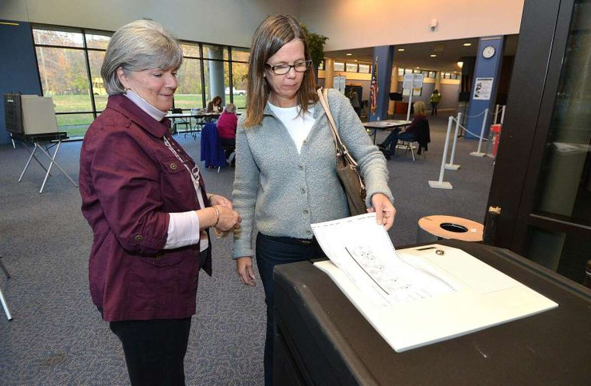 Machine tender Susie Gross watches at Kadee Alonso casts her vote at Wilton High School District 1 on Election Day.