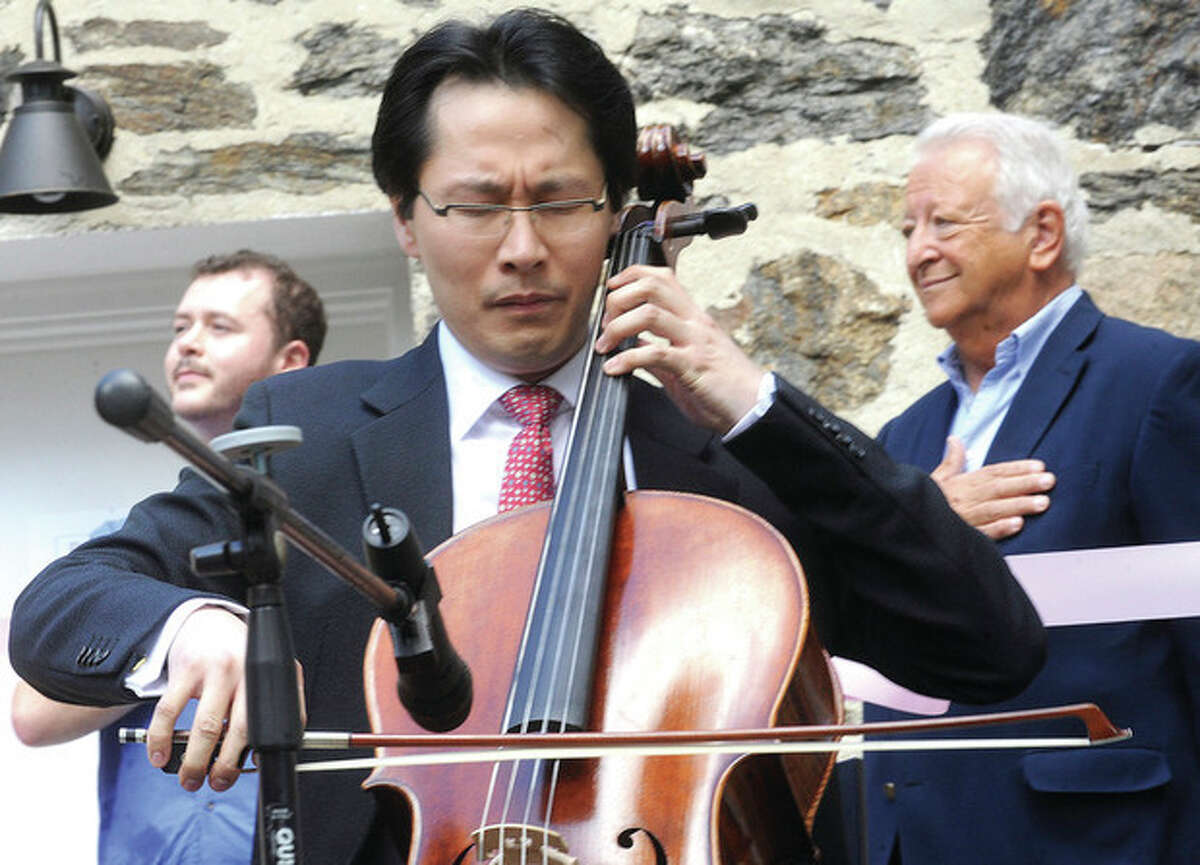 Hour photo/Matthew Vinci Kenneth Kuo, President/CEO of Rental instrument, LLC plays the National Anthem on his cello Sunday at the new loction in Norwalk for his instrument rental company.