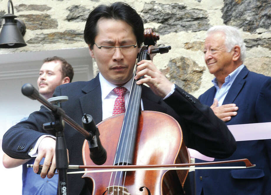Hour photo/Matthew VinciKenneth Kuo, President/CEO of Rental instrument, LLC plays the National Anthem on his cello Sunday at the new loction in Norwalk for his instrument rental company.