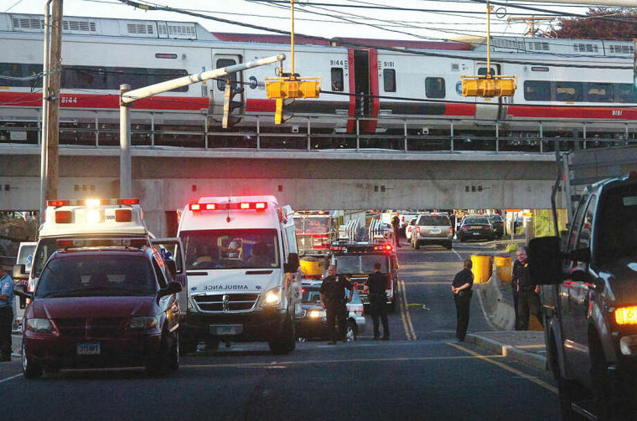 Hour Photo/Alex von Kleydorff. A Metro North train rests heading south as emergency personel gatheron Fairfield Ave underneath to tend for victims after two trains collided in Bridgeport Friday night