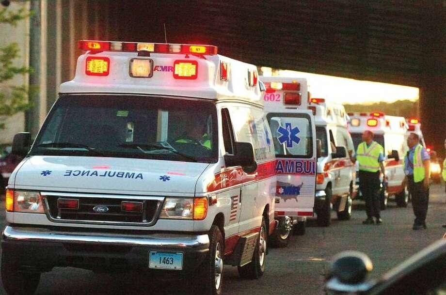 Hour Photo/Alex von Kleydorff. Ambulances wait after two Metro North trains collided in Bridgeport Friday night.