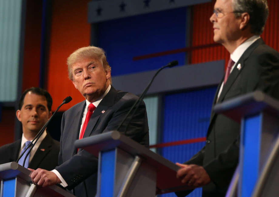 Republican presidential candidate Donald Trump looks toward Jeb Bush, right, as Scott Walker watches during the first Republican presidential debate at the Quicken Loans Arena Thursday, Aug. 6, 2015, in Cleveland. (AP Photo/Andrew Harnik)