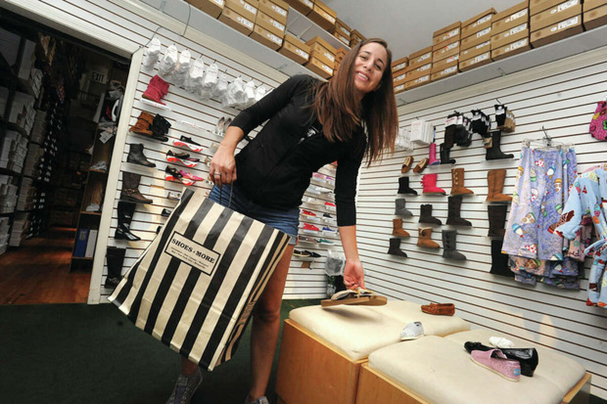 Hour photo / Matthew Vinci Stephanie Zepeda buys six pairs of shoes Sunday at Shoes 'N' More in Westport.