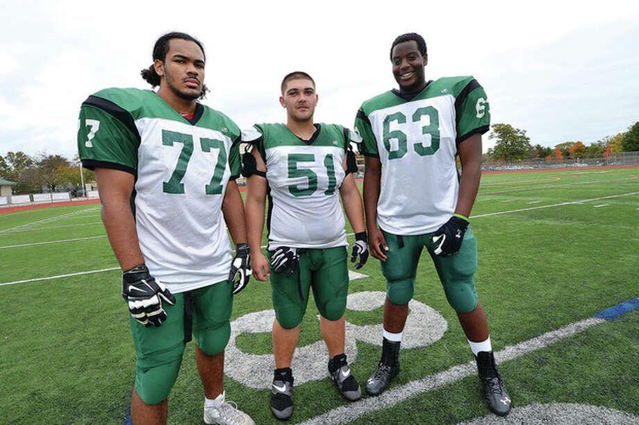 Hour Photo/Alex von KleydorffNorwalk football defensive linemen, from left, Corey Barrett, Tommy La Rosa, and Evan Adams are a dominant unit up front.