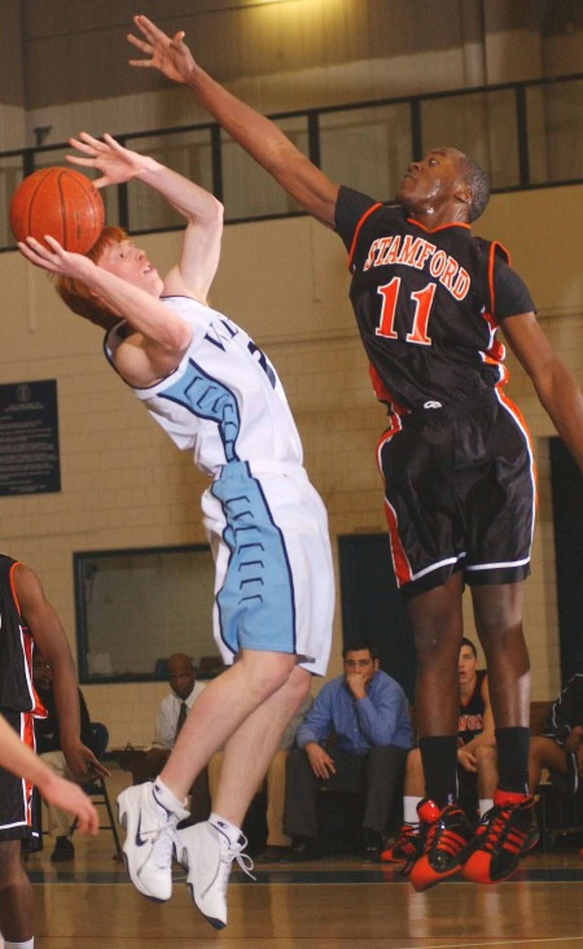 Photo by John Nash - Stamford''s Chris Evans, right, changes the shot of Wilton''s Jared Wyman.