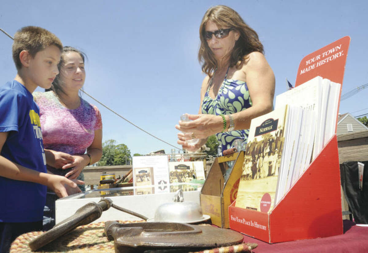 """Hour photo/Matthew Vinci Lisa Wilson Grant at Overton's restaurant in Norwalk signs her latest book """"Norwalk"""" as part of Arcadia Publishing's """"Images of America"""" series. Katia Piorkowski and her son Paul, 11, look at artifacts Lisa has collected that are local to the area."""