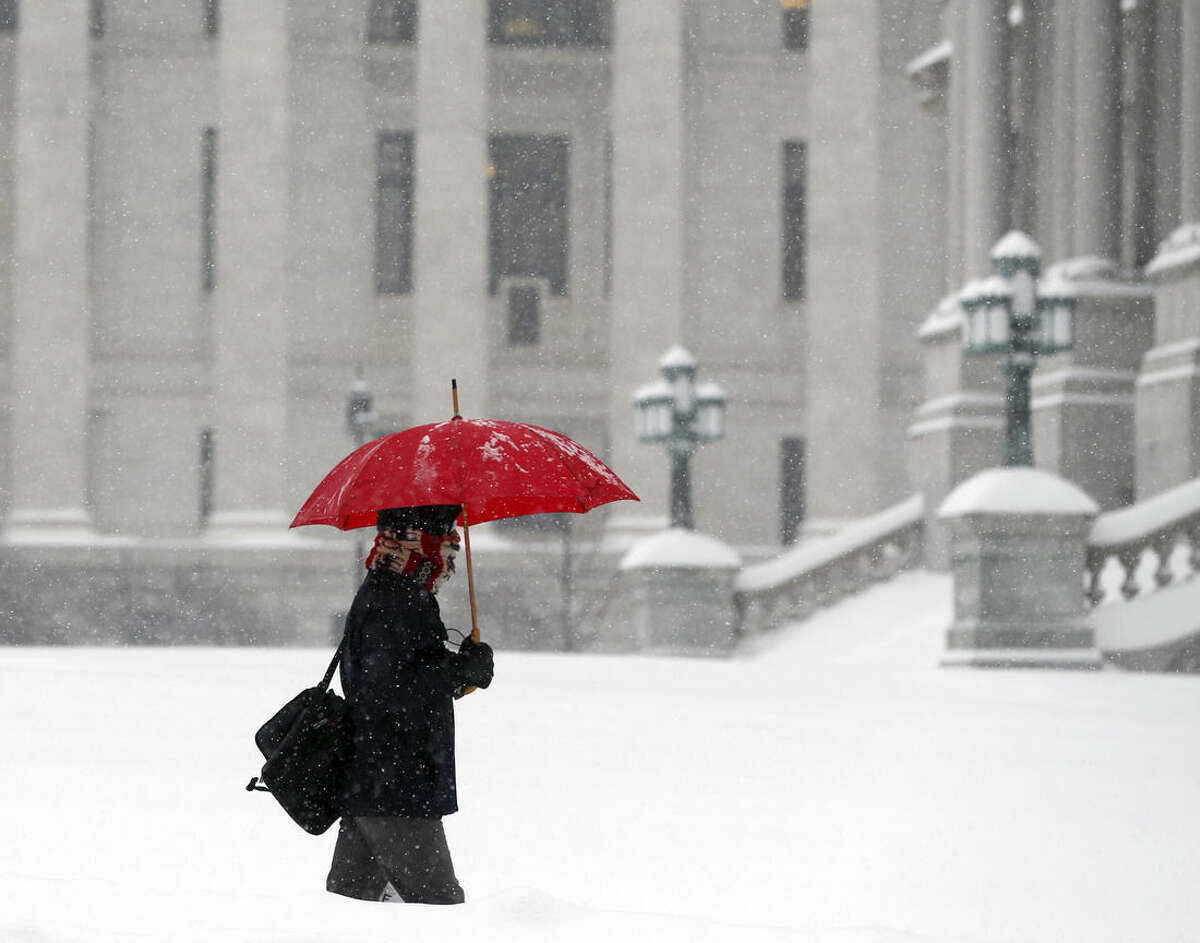 A pedestrian walks through morning snow past the State Education Building, background, and the Capitol, Monday, Feb. 9, 2015, in Albany, N.Y. Another round of snowy weather is starting off the week in much of upstate New York, with scores of schools closed and commuters facing a messy trip to work. (AP Photo/Mike Groll)