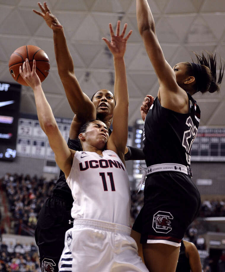Connecticut's Kia Nurse, center, is fouled by South Carolina's Alaina Coates, left, as A'ja Wilson, right, defends during the first half of an NCAA college basketball game, Monday, Feb. 9, 2015, in Storrs, Conn. (AP Photo/Jessica Hill)