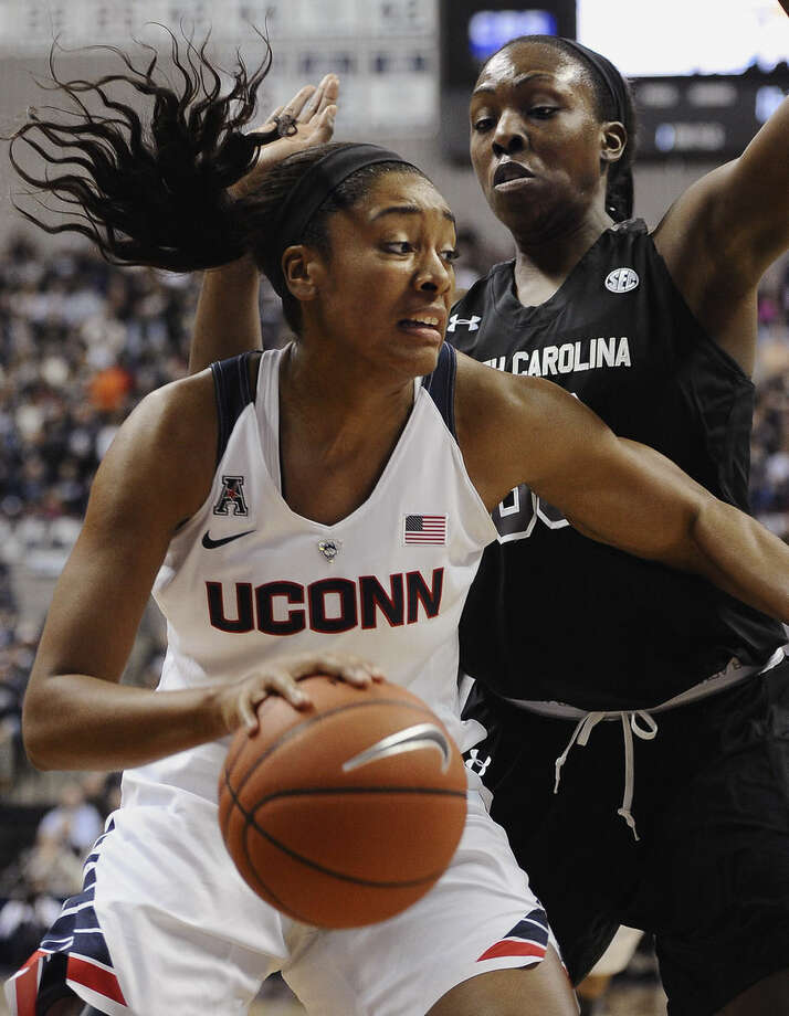 Connecticut's Morgan Tuck, left, drives to the basket as South Carolina's Elem Ibiam, right, defends during the first half of an NCAA college basketball game, Monday, Feb. 9, 2015, in Storrs, Conn. (AP Photo/Jessica Hill)