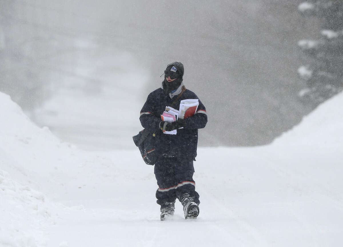 Jake Cote, a U.S. Postal Service carrier, makes his way up a hill, Monday, Feb. 9, 2015, in Utica, N.Y. The third major winter storm in less than two weeks inflicted fresh snow across New England and portions of New York state on Monday. (AP Photo/Observer-Dispatch, Mark DiOrio)