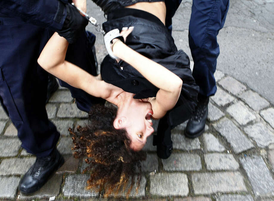 A Femen activist is taken away by police officers as she protests Tuesday, Feb. 10, 2015 in front of the Lille courthouse in Lille, northern France, where Dominique Strauss-Kahn goes on trial for sex charges in France. The former head of the International Monetary Fund, whose career went down in flames amid accusations of sexually assaulting a hotel maid in New York, is facing similarly shocking charges in France: aggravated pimping and involvement in a prostitution ring operating out of luxury hotels. (AP Photo/Michel Spingler)