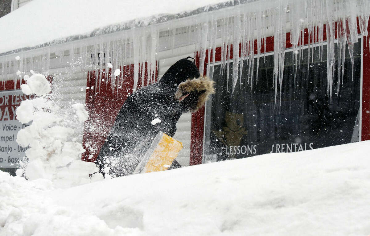 Corbit Larson clears snow in front of icicles hanging off his Centre Music store Monday, Feb. 9, 2015, in Framingham, Mass. A long duration winter storm that began Saturday night remains in effect for a large swath of southern New England until the early morning hours Tuesday. (AP Photo/Bill Sikes)