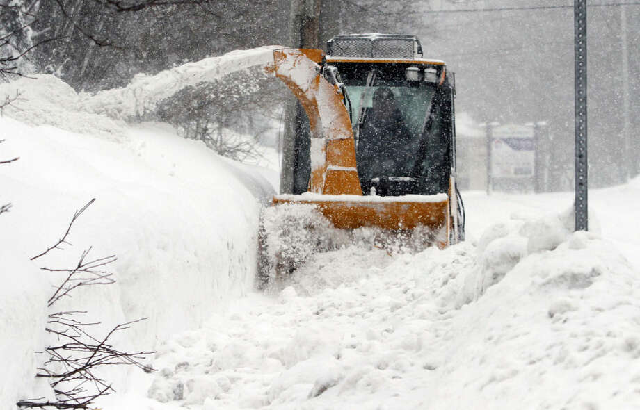 FILE - In this Feb. 9, 2015 file photo, city worker Jeff D'Amico clears snow from a sidewalk in Marlborough, Mass. State and local governments in southern New England have spent millions in plowing and other inclement weather expenses during the series of storms, and retail businesses are struggling as messy roads and traffic jams have driven consumers away. (AP Photo/Bill Sikes, File)