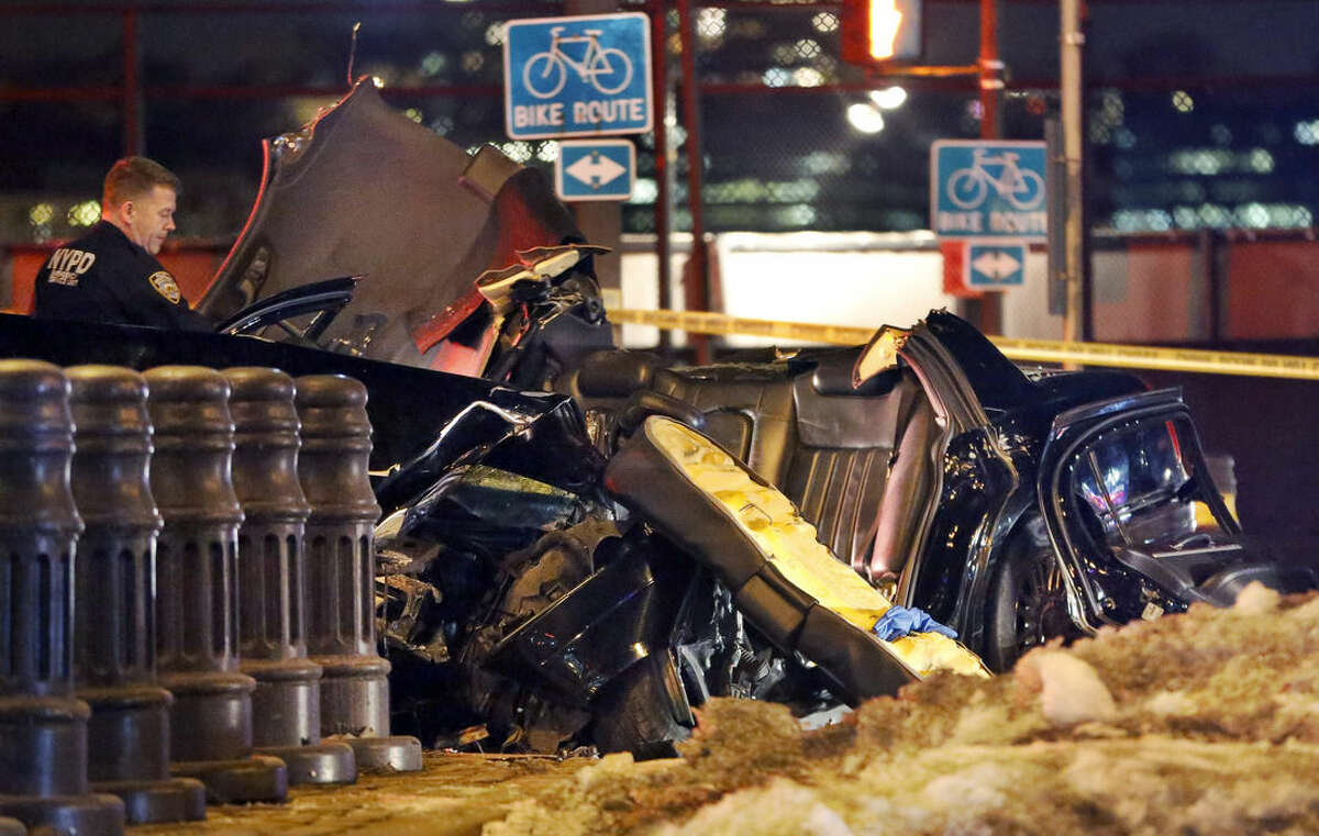 """A police officer surveys the scene of an accident following a collision in New York, Wednesday, Feb. 11, 2015, that killed longtime """"60 Minutes"""" correspondent Bob Simon. Simon, who was 73, covered riots, Academy Award-nominated movies and wars and was held captive for more than a month in Iraq two decades ago. (AP Photo/Kathy Willens)"""