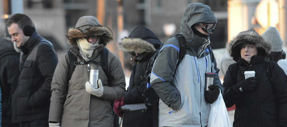 Commuters wait at the Arlington Heights, Ill. Metra train station as a cold snap took hold in the suburbs of Chicago on Thursday, Feb. 19, 2015. (AP Photo / Daily Herald, Joe Lewnard )
