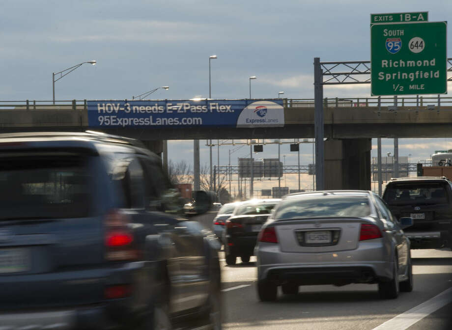 ADVANCE FOR SATURDAY, FEB. 21, 2015, AND THEREAFTER - FILE - In this Dec. 10, 2014, file photo, a banner hangs on an overpass on Interstate 395 advertising the new I-95 Express Lanes in Alexandria, Va. As legislatures convene across the country, lawmakers and governors are grasping for ways to address an aging network of roads, highways and bridges during an era in which federal money for such projects has remained stagnant or declined. In Virginia, the new I-95 express lanes were funded in part by private investors who have a long-term contract to collect tolls. (AP Photo/Molly Riley, File)