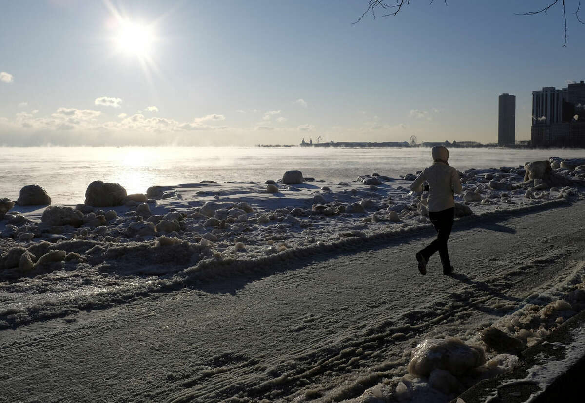 A runner jogs along Lake Michigan as ice forms on the shore Thursday, Feb. 19, 2015, in Chicago. Temperatures have dipped to as low as -13 in parts of Illinois with wind chills forecast to fall to between 20 and 30 degrees below zero. (AP Photo/Kiichiro Sato)