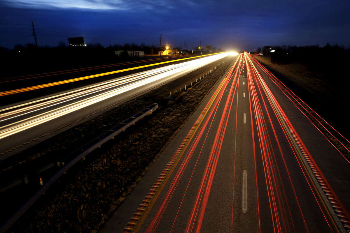 ADVANCE FOR SATURDAY, FEB. 21, 2015, AND THEREAFTER - In this photo made with a 25 second exposure on Thursday, Feb. 12, 2015, vehicles travel along Interstate 70 in Wright City, Mo. Built in the 1950s and '60s with an expected life of 20 years, a 200-mile span of the four-lane interstate between suburban St. Louis and Kansas City is crumbling beneath its surface as it carries more than 30,000 vehicles a day on many of its rural stretches. (AP Photo/Jeff Roberson)