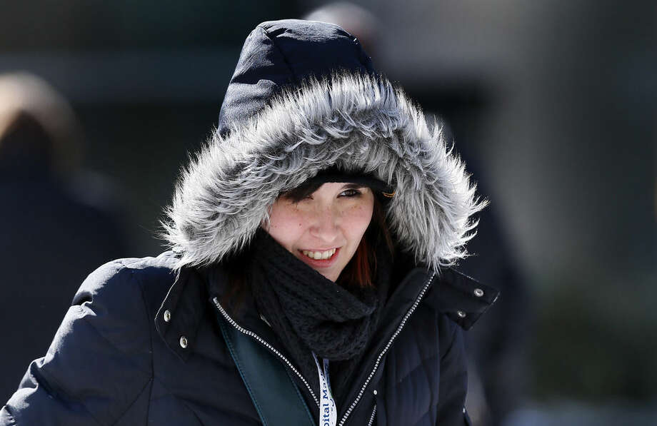 Jessie Saputo bundles up while walking in Detroit Thursday, Feb. 19, 2015. The National Weather Service says the temperature dropped to 5 below zero Thursday morning at Detroit Metropolitan Airport in Romulus, one degree below the previous Detroit record for the date from 1936. (AP Photo/Paul Sancya)