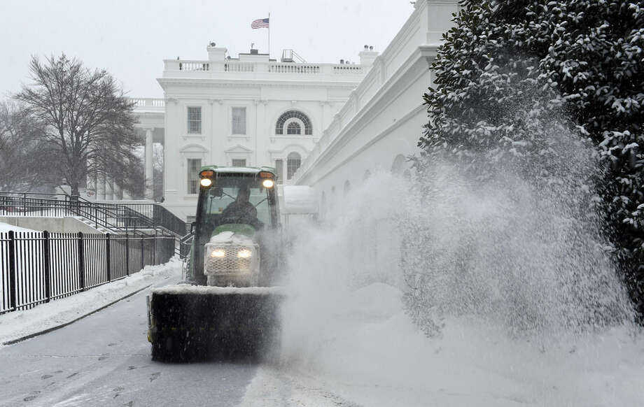 Snow is cleared on the North side of the White House in Washington, Saturday, Feb. 21, 2015. The National Weather Service is calling for 3 to 6 inches of snow and then a trace to a small amount of ice in the area. The cold ground is allowing snow to stick faster, making it difficult for road crews to keep up. (AP Photo/Susan Walsh)