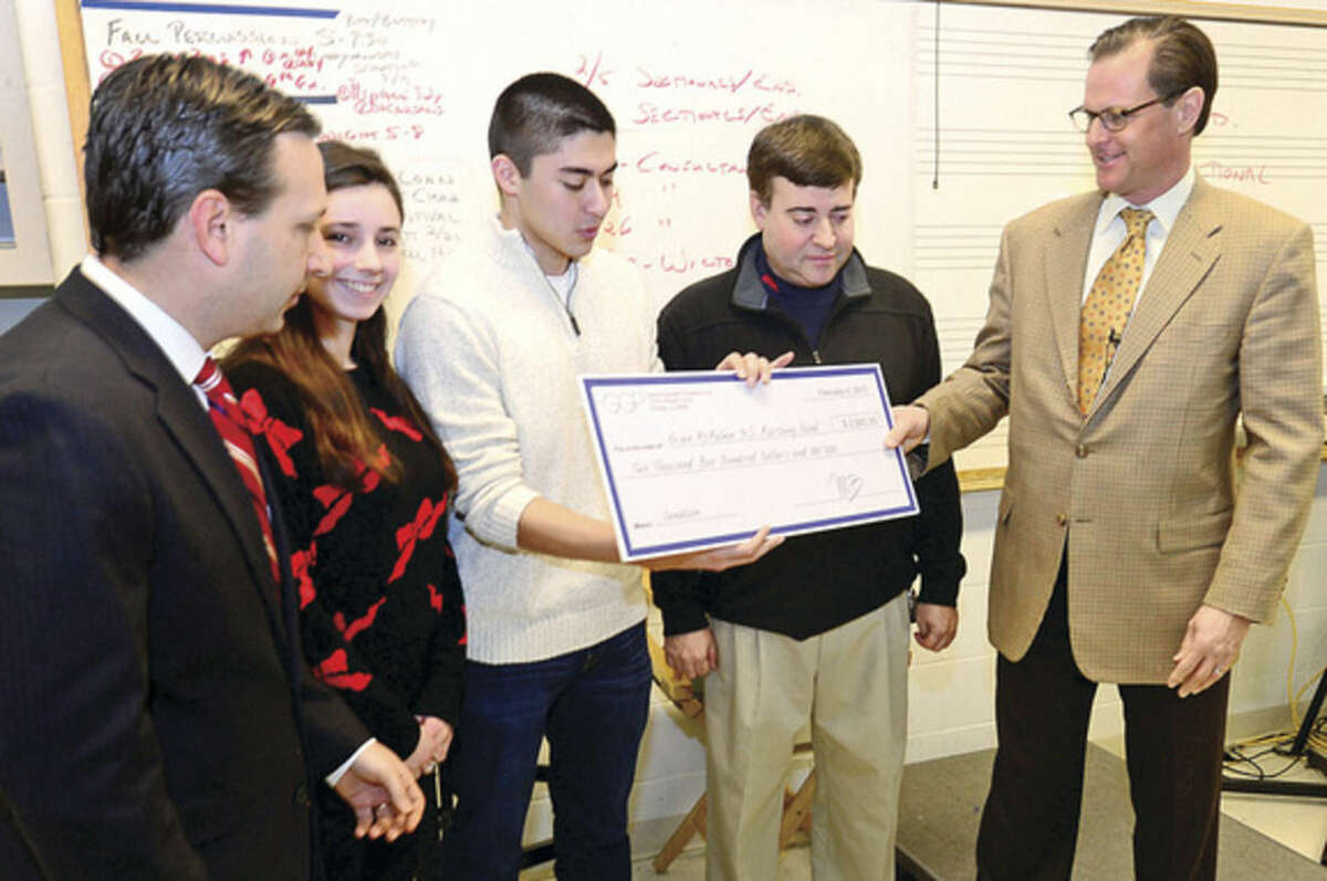 """Hour photo / Erik Trautmann State Senator Bob Duff, left, and Doug Adams, Senior Director, General Growth Properties, right, visit the Brien McMahon High School Band to present the Band Director Ron Secchi, second from right, and drum majors Elle Buelesbach and Sam Starkman with a check for $2,500, to make up for the loss of revenue after a power outage forced the school to cancel the remaining portion of a Brien McMahon High School Band's largest annual fundraiser, the """"Celebration of Sound,"""" band competition."""