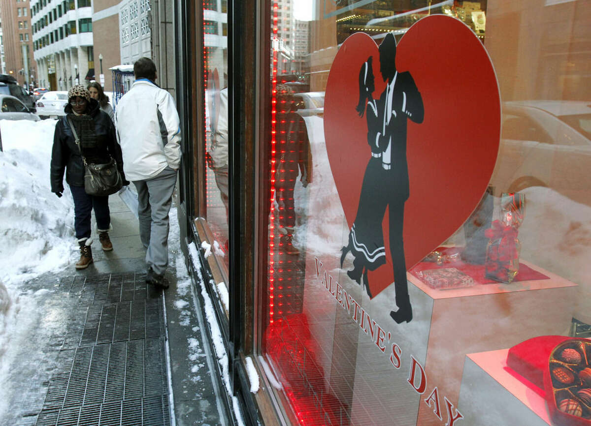 In this Feb. 11, 2015 file photo, commuters walk past piles of snow in front of Au Chocolat in downtown Boston. During the series of storms, some retail businesses are struggling as messy roads and traffic jams have driven consumers away. (AP Photo/Bill Sikes)