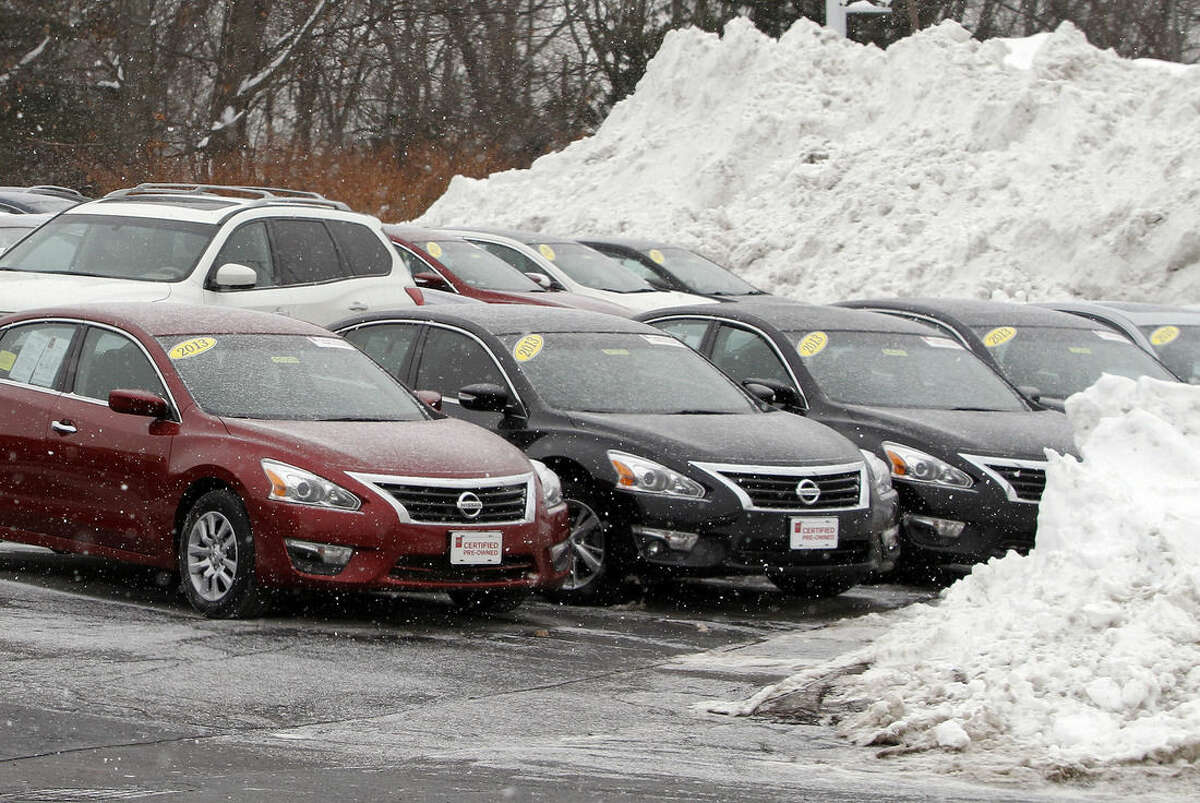 In this Feb. 12, 2015 photo, cars share space with piled snow at an auto dealership in Marlborough, Mass. Car dealerships are among the retailers hoping for a strong President's Day weekend to help make up for an abysmal sales month. But standing in their way is another major storm that is predicted to dump over a foot of new snow in the Boston area Saturday into Sunday. (AP Photo/Bill Sikes)