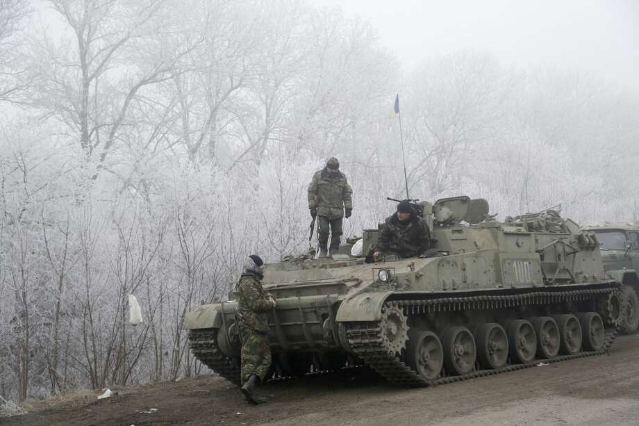 Ukrainian government soldiers rest by armored vehicle on the road between the towns of Dabeltseve and Artemivsk, Ukraine, Sunday, Feb. 15, 2015. International attention will be focused in the coming days on the strategic railway hub of Debaltseve, where Ukrainian government forces have for weeks been fending off severe onslaughts from pro-Russian separatists. A cease-fire was declared in eastern Ukraine, kindling slender hopes of a reprieve from a conflict that has claimed more than 5,300 lives. (AP Photo/Petr David Josek)