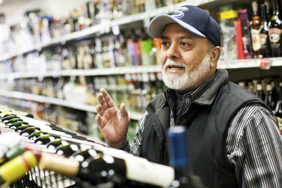 Above, Kalwant S. Bhullar, owner of Wall Street Wine & Liquor, gives his opinion Sunday on Gov. Dannel Malloy's proposal to loosen Connecticut's alcohol sales laws. Below, liquor on display at Bev Max in Norwalk Sunday afternoon.
