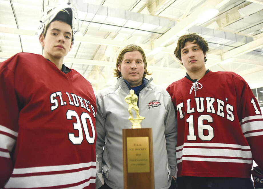 Photo by John NashSt. Luke's goaltender Brian Kollar, left, and Tyler Keith, right, stand alongside their coach Ron Carlucci as the trio displays the Fairchester Athletic Association's ice hockey championship trophy. The trio are all Stamford residents who helped lead the Storm to the title.