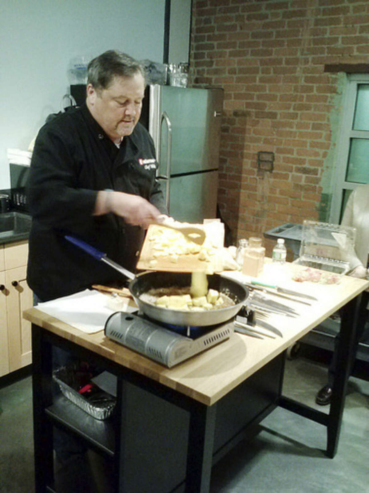 Photo by Frank Whitman Chef Mike prepares Pineapple Foster at Wusthof in Norwalk.
