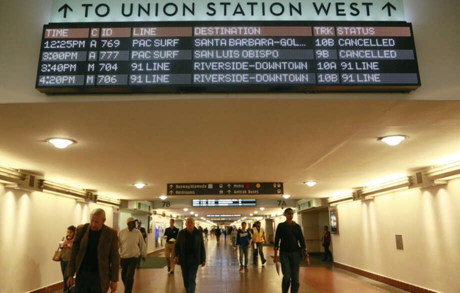 A Southern California passenger rail timetable shows the cancelled schedules of the Amtrak Pacific Surfliner at Union Station downtown Los Angeles Tuesday, Feb. 24, 2015, after three cars of a Southern California Metrolink commuter train derailed and tumbled onto their sides after a collision with a truck on tracks in Ventura County northwest of Los Angeles. (AP Photo/Nick Ut)