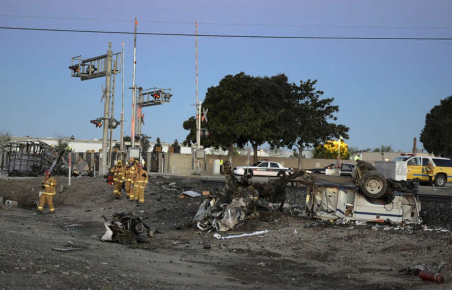 Firefighters arrive to attend to injured passengers at the scene of a Metrolink accident, Tuesday, Feb. 24, 2015, in Oxnard, Calif. Three cars of a Southern California Metrolink commuter train have derailed and tumbled onto their sides after a collision with a truck on tracks in Ventura County, northwest of Los Angeles. (AP Photo/Johnny Corona)