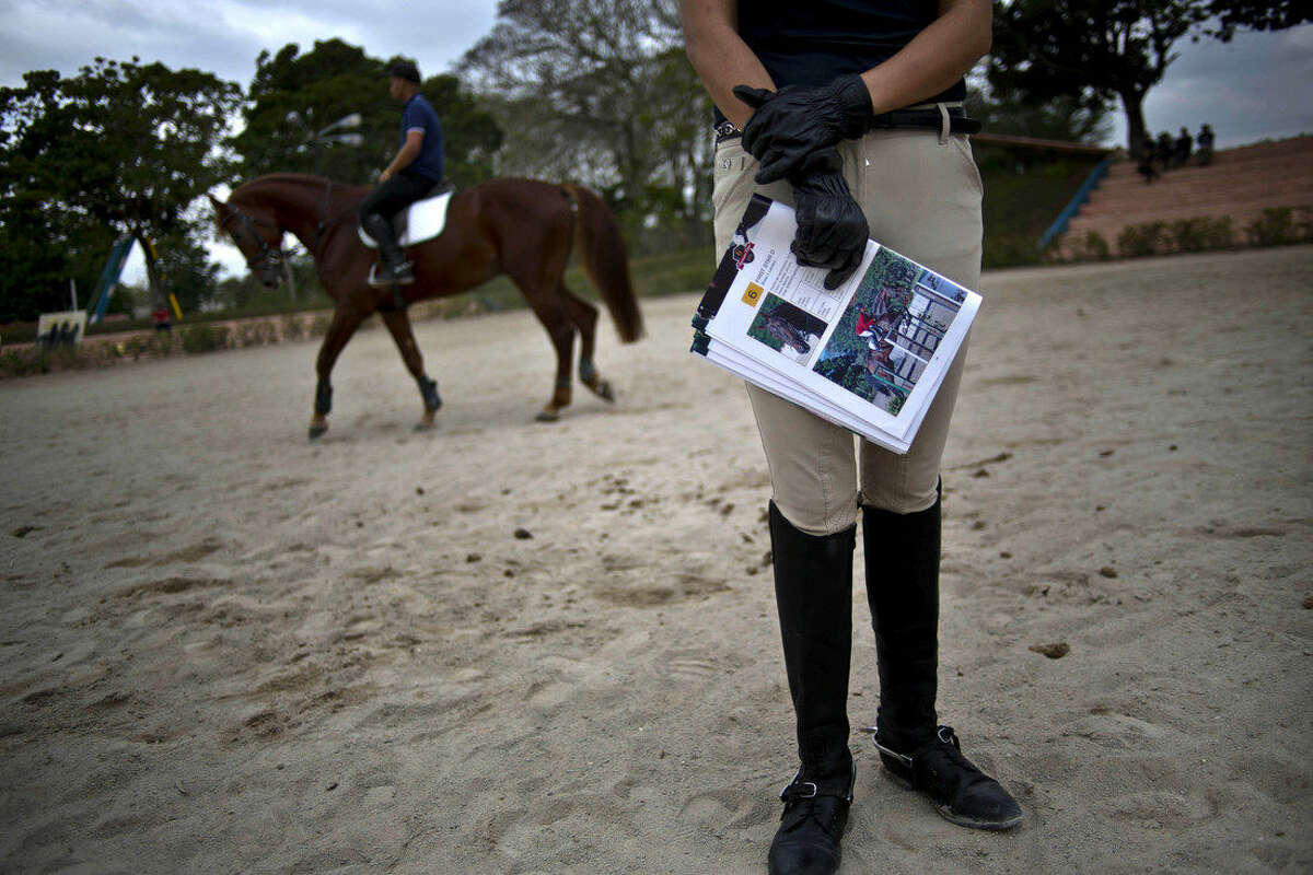 """In this Jan. 30, 2015 photo, Cecilia Pedraza, a Mexico City collector who bought several of Dutch Warmbloods horses, holds a magazine that lists horses for auction at the National Equestrian Club in Lenin Park on the outskirts of Havana, Cuba. """"The great advantage is that they are already in the Americas,"""" said Pedraza. """"In addition, they have been trained very well. They are advanced for their age, very well-behaved, perform concentrated jumps and have excellent blood lines."""" (AP Photo/Ramon Espinosa)"""