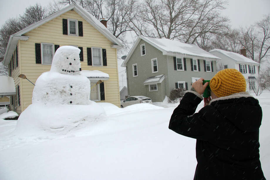 Anna Vincelli, 45, photographs a two-story snowman built by her neighbor in Irondequoit, N.Y. The region has had 84.5 inches of snow so far this winter, 11 inches above normal, according to the National Weather Service. (AP Photo/Ted Shaffrey)