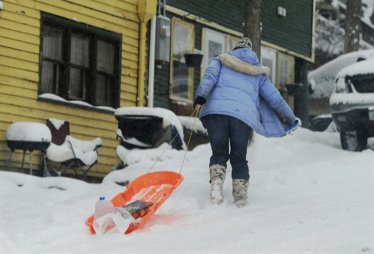 A sled is used for carrying a few conveniences home from the store in Manitou Springs, Colorado, on Sunday, Feb. 22, 2015. The Pikes Peak region has seen varying snow totals up to about 10 inches over the weekend, but forecasters predict up to two feet of snow possible for areas of the front range by the time the snow ends on Monday. (AP Photo/The Gazette, Jerilee Bennett)