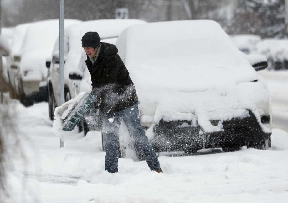 Shoveler works to clear a path after a winter storm sent temperatures plunging to single-digit levels and dumped up to a foot of snow Sunday, Feb. 22, 2015, in Denver. Forecasters predict that the cold and snow will persist through Monday. (AP Photo/David Zalubowski)