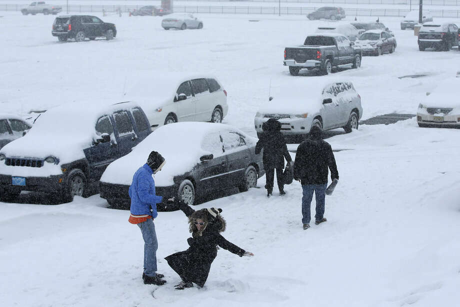 A woman is helped up after making a snow angel in a parking lot outside the Wells Fargo Center during a winter storm after an NHL hockey game between the Philadelphia Flyers and the Nashville Predators, Saturday, Feb. 21, 2015, in Philadelphia. (AP Photo/Matt Slocum)