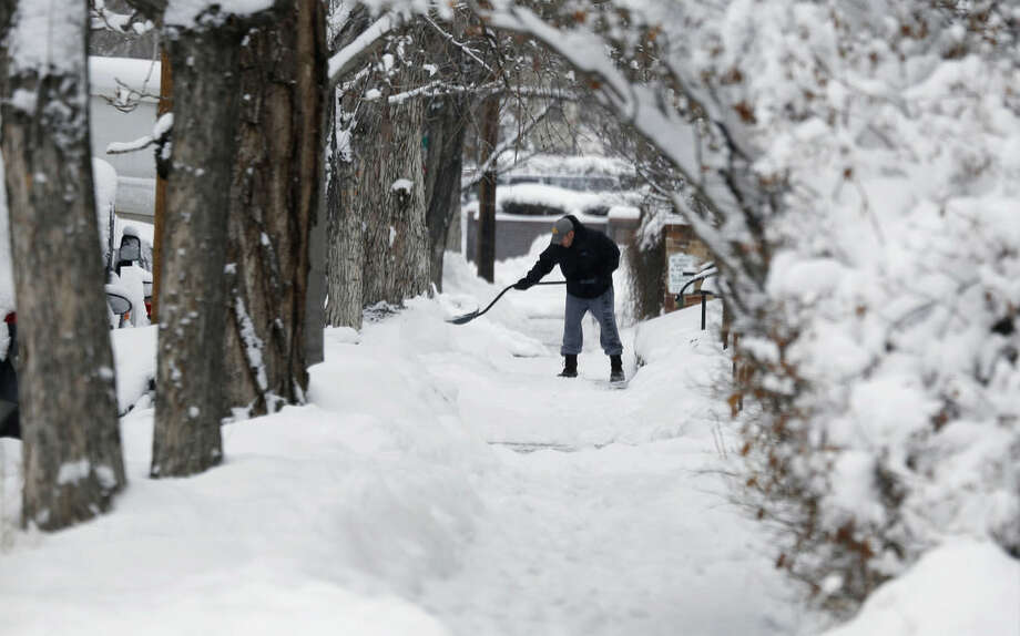 Framed by trees, a lone shoveler toils on a sidewalk after a winter storm sent temperatures plunging to single-digit levels and dumped up to a foot of snow Sunday, Feb. 22, 2015, in Denver. Forecasters predict that the cold and snow will persist through Monday before another storm sweeps over Colorado's Front Range communities Thursday. (AP Photo/David Zalubowski)